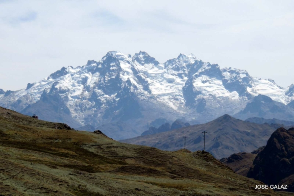 Looking over a grassy hillside at the snow-covered Andes mountains in the background