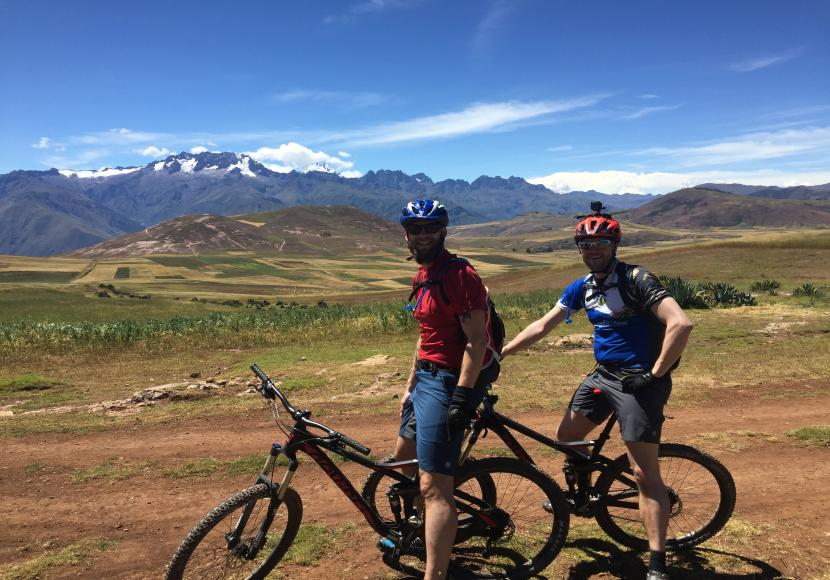 Two men sitting on their mountain bikes on a dirt track in a field in Peru with green hills and mountains in the distance