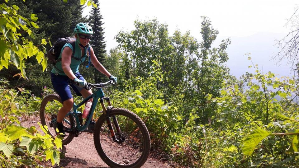 Smiling woman on mountain bike going down slight incline on dirt trail surrounded by mountain foliage on left