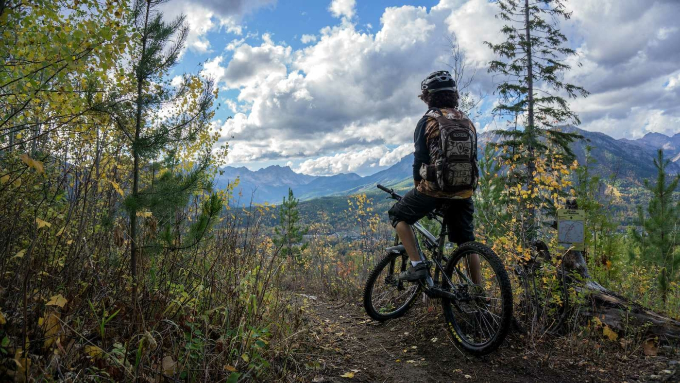 Person sitting still on their mountain bike at a mountain lookout with mountain valley in distance and blue sky overhead