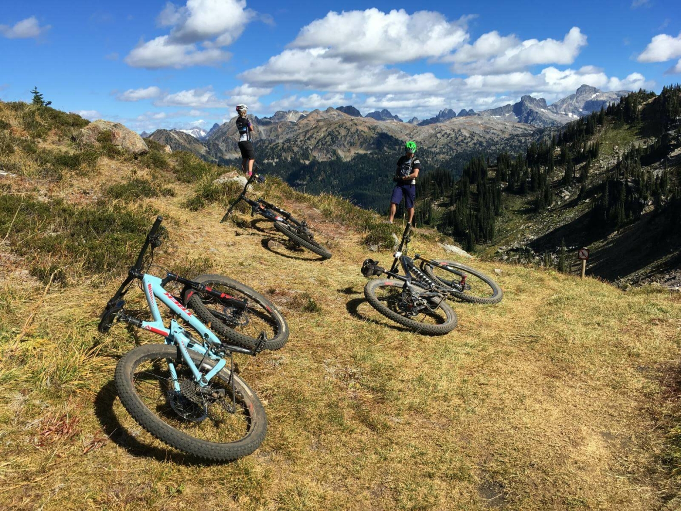 Three mountain bikes laying on the ground and two mountain bikers standing and looking out over the mountain valley