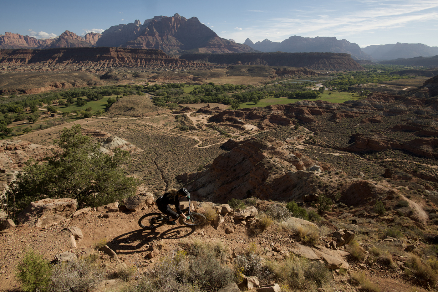 Overhead view of person riding a mountain bike on a red dirt trail surrounded by red sandstone cliffs