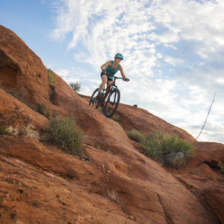 Looking upwards at mountain biker coming down steep red rock hill with blue sky and scattered clouds above them