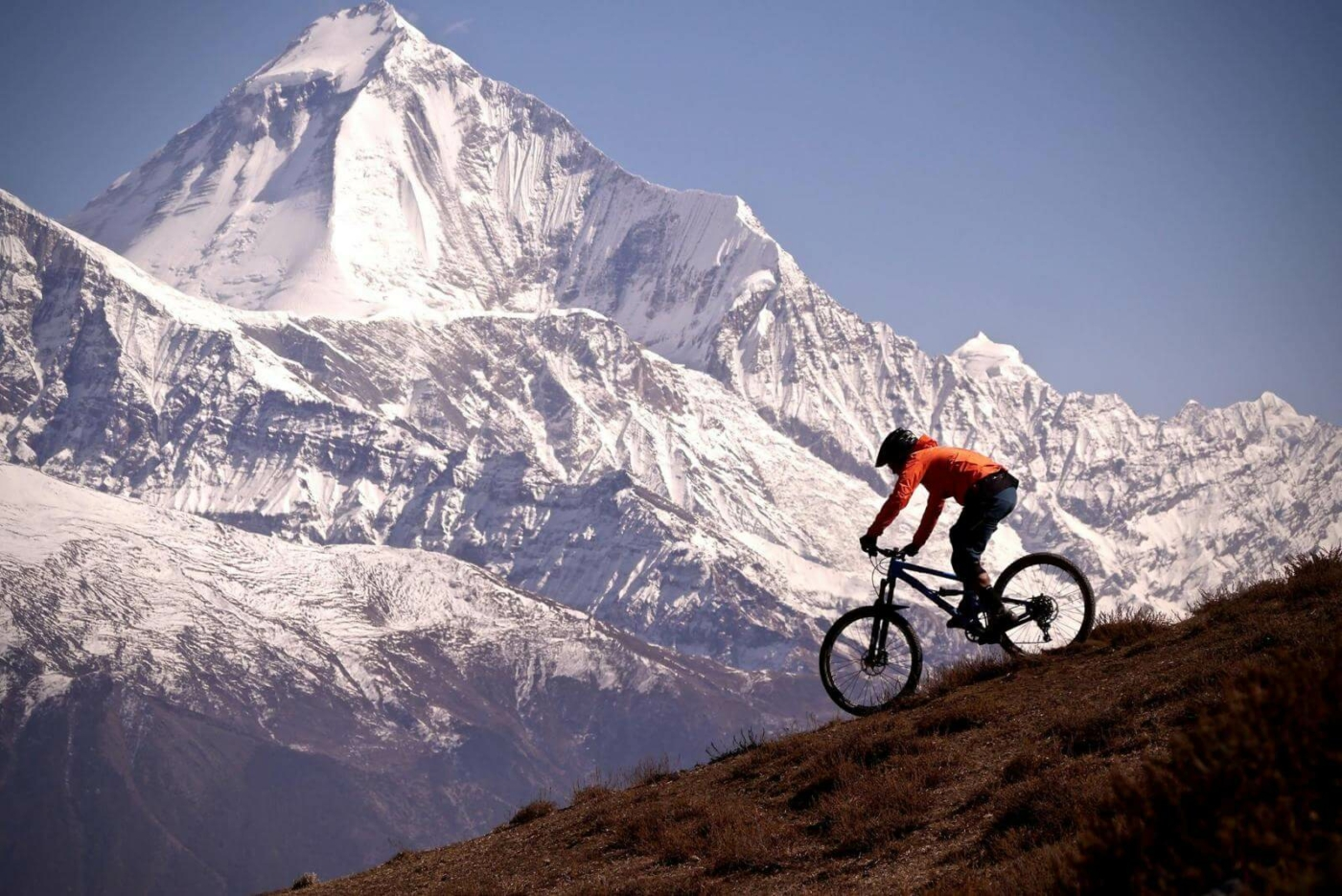 Mountain Biker going down a steep hill with snow-covered mountain in the background
