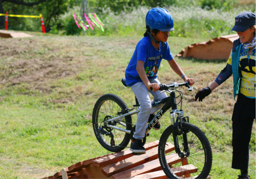 A Kid Around Eleven Years Old Being Coached by an Adult Standing Next to Him While He Learns How to Ride a Mountain Bike Up a Small Ramp