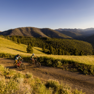 Two mountain bikers riding side by side on wide path surrounded by deep green grass and rolling hillsides