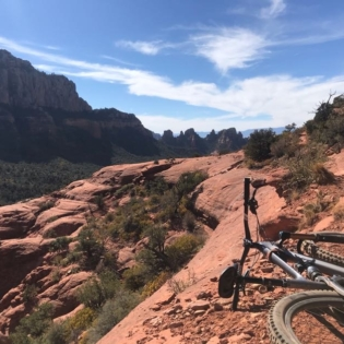 A mountain bike laying on a red desert trail to the right with more red desert rock all around