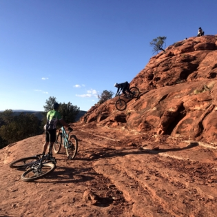 Two people riding across huge red rock while one rides down steep descent and another stands next to bike watching
